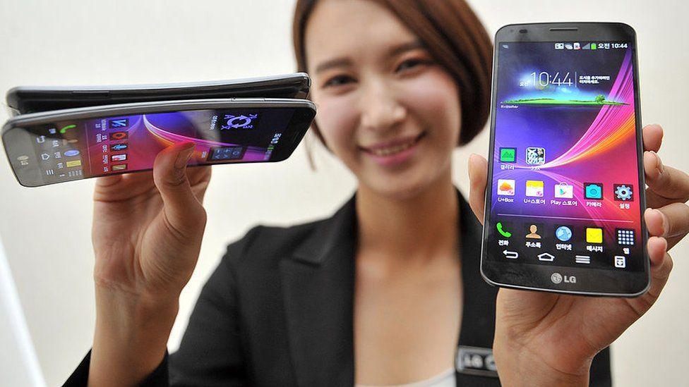 Mujer mostrando un teléfono celular LG